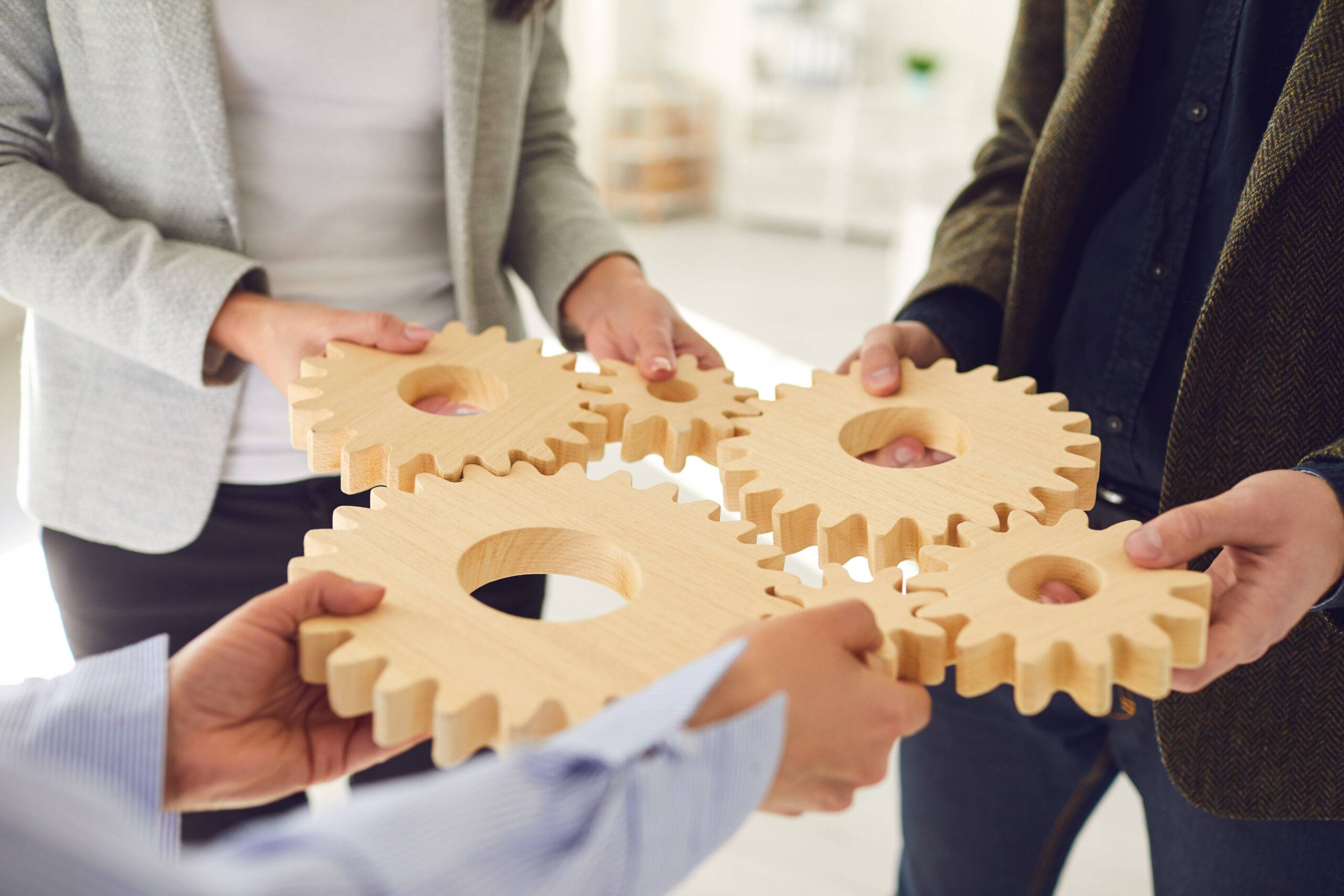A group of business people holds wooden wheels with teeth in their hands on an office white table. Business cooperation concept business team innovation strategy integration teamwork contract integration.